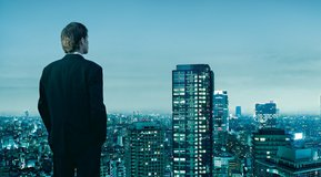 Man looking over the skyline from Tokyo in the evening.